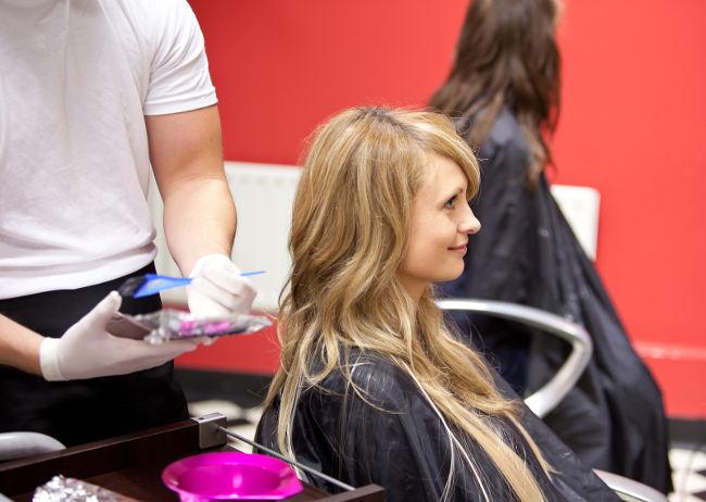 девушка красит волосы в салоне красоты