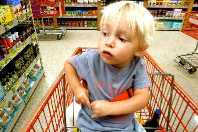 ребенок в тележке в супермаркете