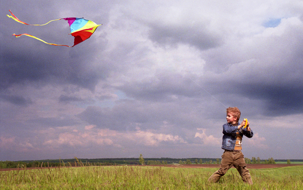 мальчик запускает воздушного змея