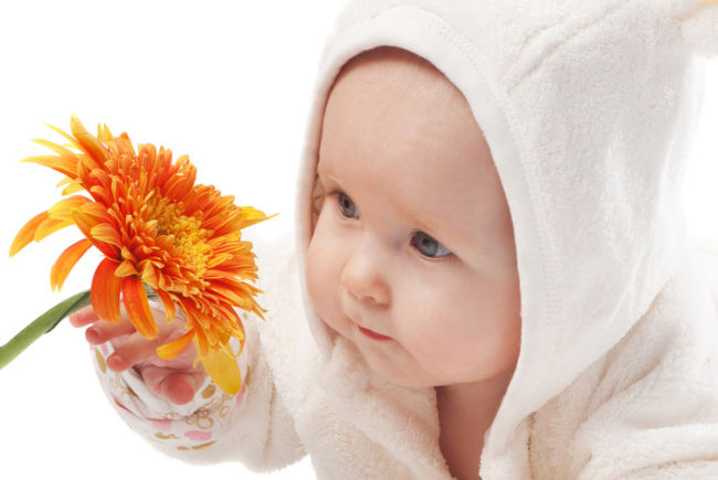 ребенок смотрит на цветок