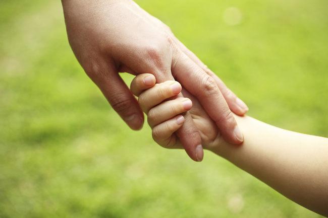 мама держит ребенка за руку